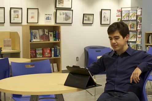 photo d'un usager utilisant une tablette numérique du Centre de Ressources.